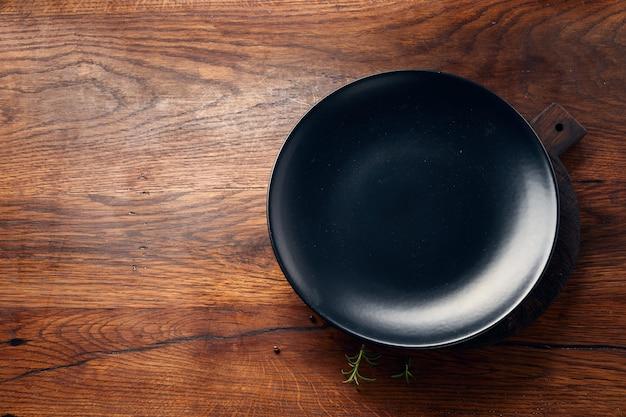 コピースペースを持つ木製テーブルに空の黒いプレート。上面図。