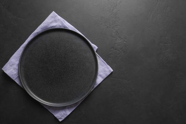 黒いキッチンの背景にライラックタオルで空の黒い皿。デザインのためのスペース。上からの眺め。