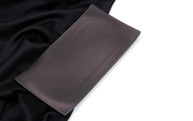 シルクのテーブルクロスの質感を持つ空の黒い長方形のモダンなセラミックプレート