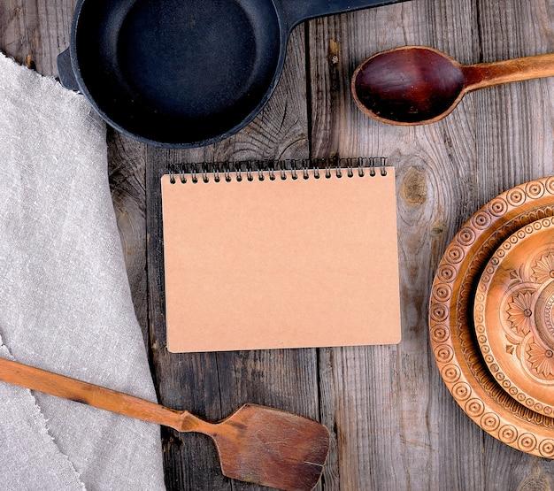 空の黒い丸いフライパン、ハンドルと紙のノート