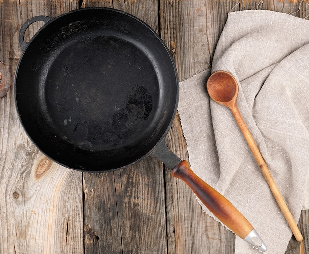 Empty black round frying pan with  handle and spoon