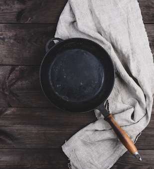 Empty black round frying pan with wooden handle and gray linen kitchen napkin