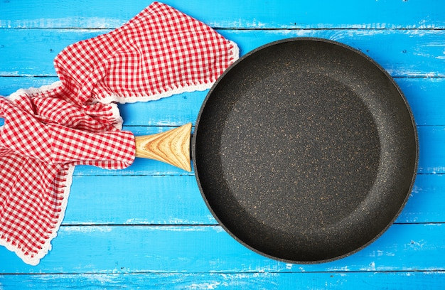 Empty black round frying pan with wooden handle and red kitchen napkin