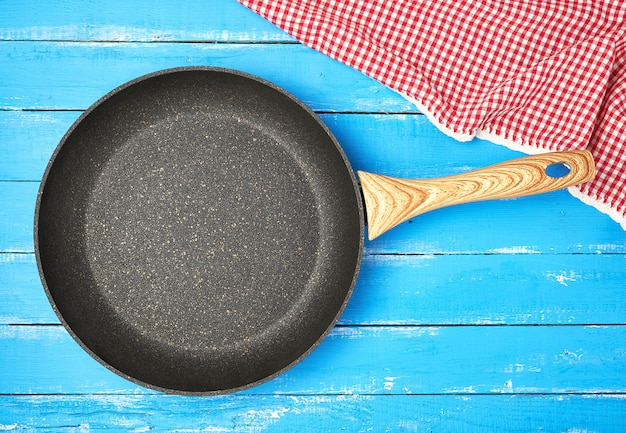 Empty black round frying pan with wooden handle