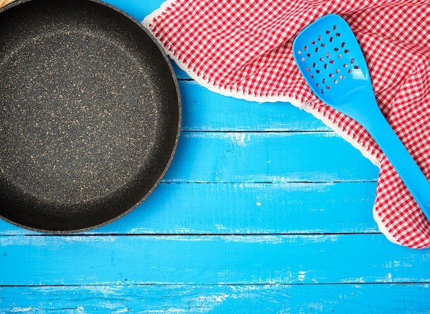 Empty black round nonstick frying pan with handle on blue wood
