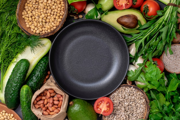 Empty black round plate with set healthy and vegan food groats, seeds. healthy and vegetarian menu of  concept
