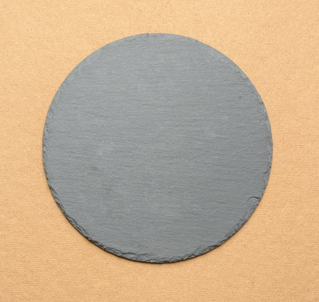 Empty black round slate kitchen board on a brown background, top view