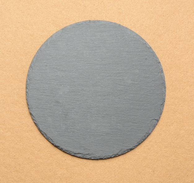 Пустая черная круглая шиферная кухонная доска на коричневом фоне, вид сверху