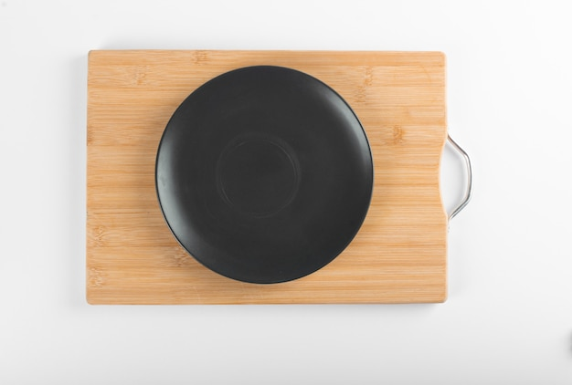 An empty black saucer on a wooden board