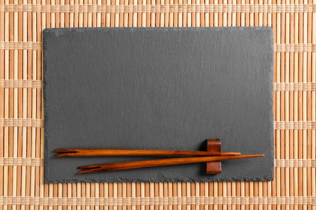 Empty black slate plate with chopsticks for sushi on wooden.