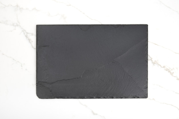 Empty black slate tray plate on white marble background. top view. mock up