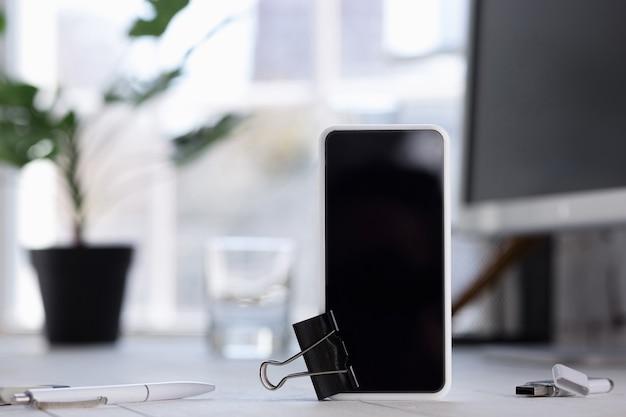 ぼやけた壁に空の黒いスマートフォン画面。コピースペース、広告、オフィス、ビジネススタイルのためのネガティブスペース。