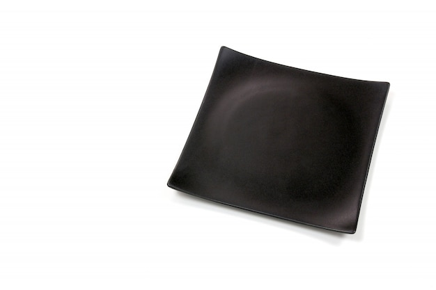 Empty black square ceramic plate with rough texture, isolated on white background