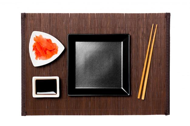 어두운 대나무 매트에 초밥, 생강, 간장 젓가락으로 빈 검은 사각형 접시. 디자인을위한 복사 공간이있는 평면도