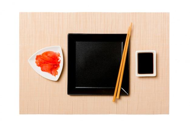 Пустая черная квадратная тарелка с палочками, имбирем и соевым соусом на желтой бамбуковой циновке