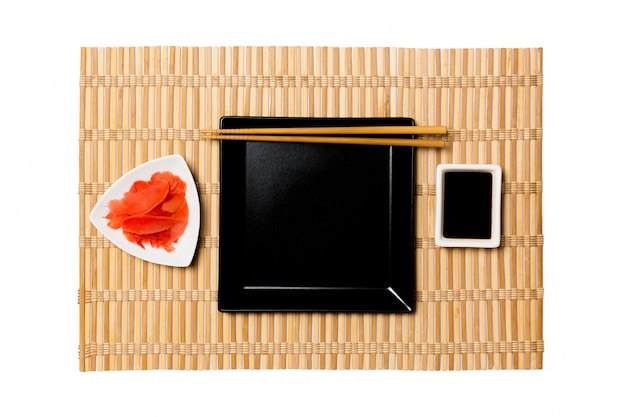 Empty black square plate with chopsticks for sushi, ginger and soy sauce on yellow bamboo mat
