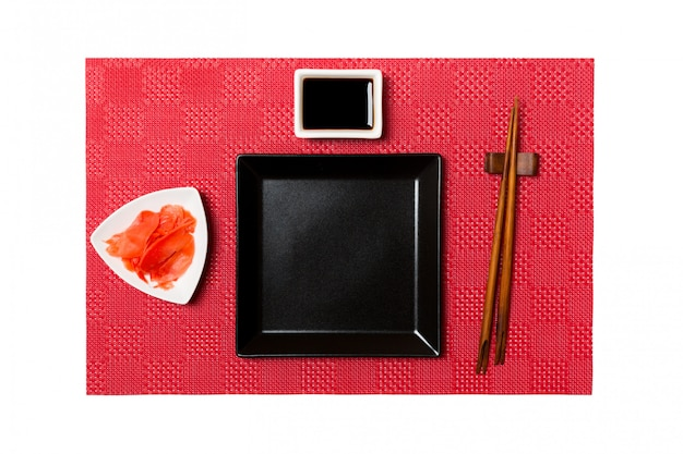 Empty black square plate with chopsticks for sushi and soy sauce, ginger on red mat sushi . top view with copyspace