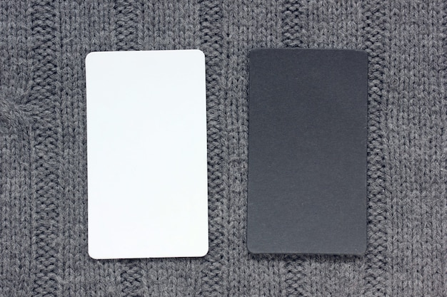 Empty black and white card on a knitted gray background, top view. mockup, scene creator.