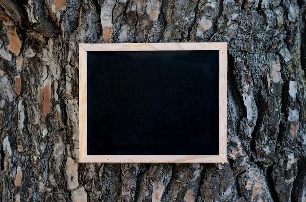 茶色のテクスチャの樹皮で松の木にぶら下がっている空の黒板