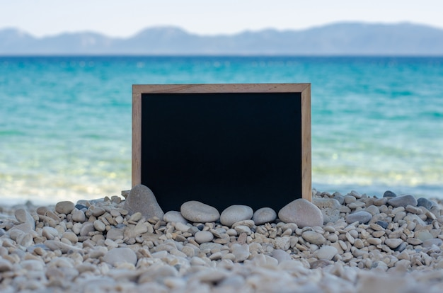Empty blackboard on a pebble beach with turquoise water and mountains in the background