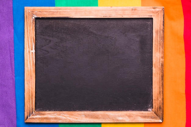 Empty blackboard on rainbow background