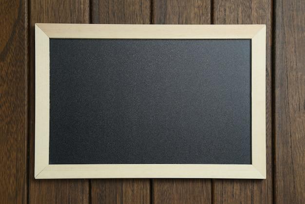 Empty blackboard on vintage wooden background