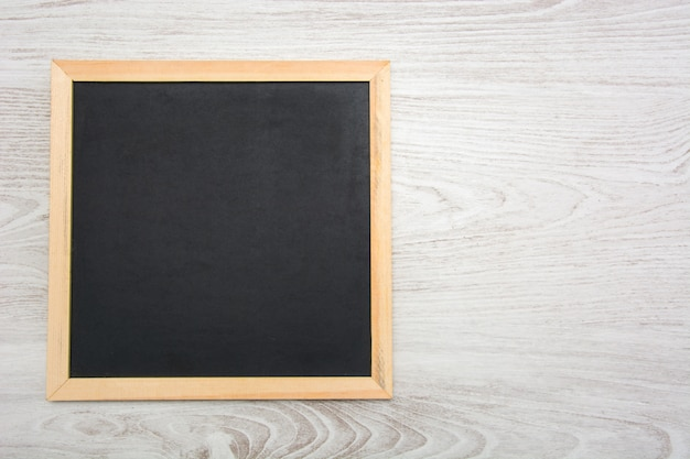 Empty blackboard on white wooden background top view copy space