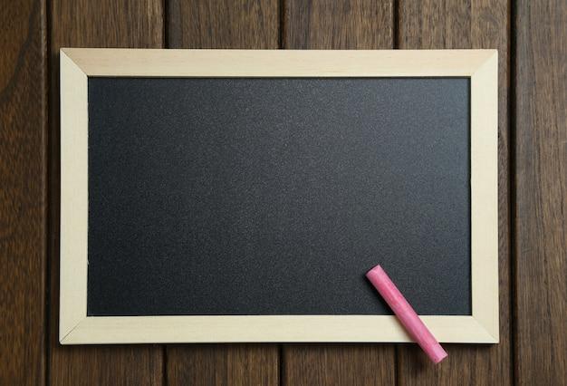 Empty blackboard with chalks on vintage wooden background