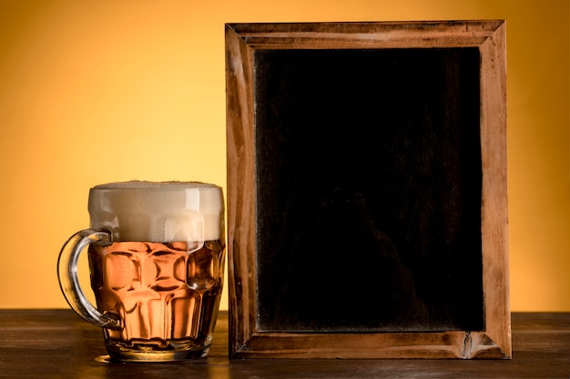 Empty blackboard with glass of beer on wooden table