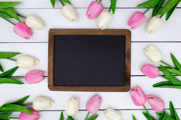 Empty blackboard with a spring composition with tulips on white wooden