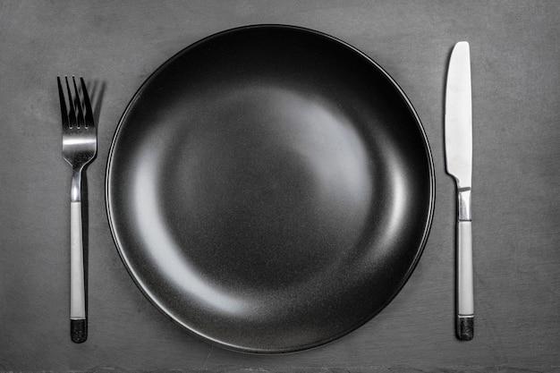 포크와 나이프 보드를 제공하는 혈암의 검은 배경에 빈 빈 검은 접시. 준비된 요리, 조리법 또는 텍스트를위한 공간을 복사합니다. 모의. 평면도. 최소한의 요리 이미지.