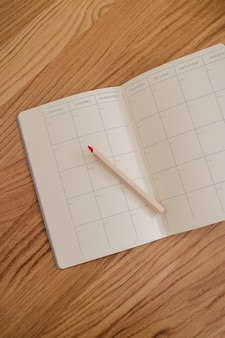 Empty and blank calendar and diary lying open viewed from above with a pencil next to it. plan and to do list concept. yellow and grey colors of the year.