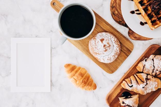 Una cornice vuota vuota vicino al croissant al forno; focacce; cialde e croissant su marmo con texture di sfondo