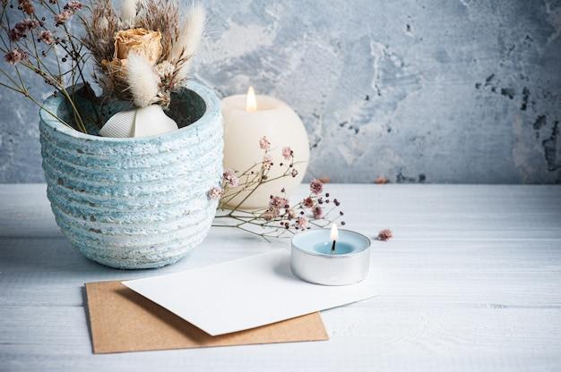 Пустая пустая записка и крафт-конверт с зажженными свечами на белом деревянном столе.