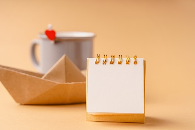 An empty blank for notes with background of a mug with a heart and a craft paper boat