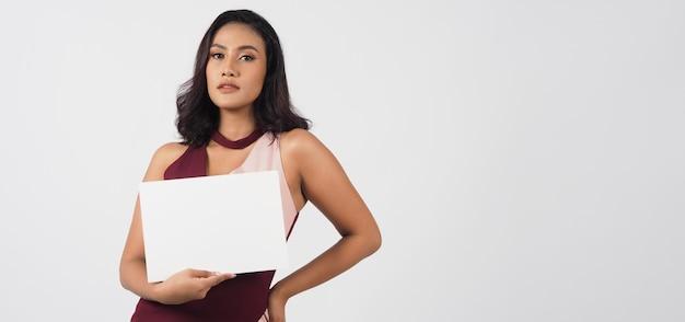 Пустой чистый лист бумаги в руке азиатской женщины. студийный портрет с белым фоном. пустое место для текста. у нее загорелая кожа.