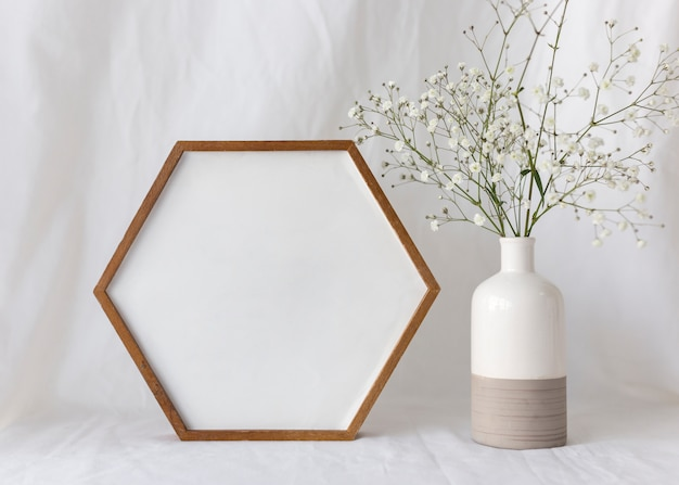 Empty blank photo frame with flower vase in front of white curtain