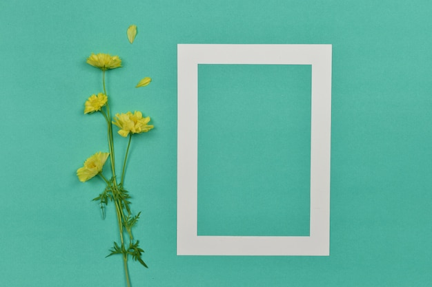 Empty blank photo paper frame with yellow flower on the side.