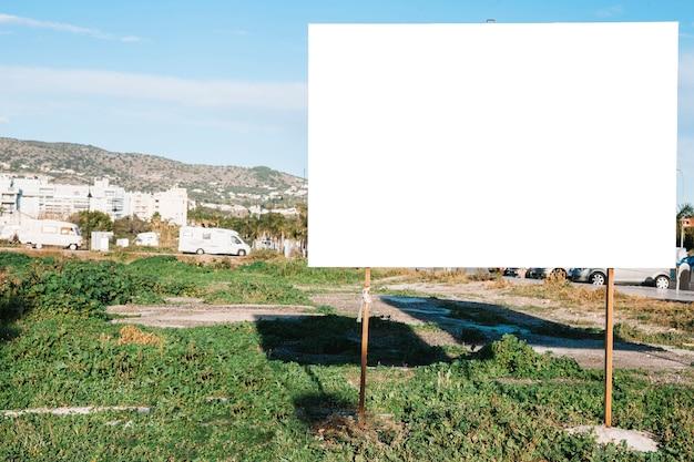 Empty blank signpost on greencity lawn
