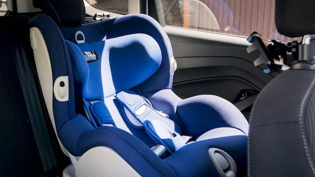 밝고 화창한 날에 자동차 뒷좌석에 빈 파란색 아기 자동차 안전 좌석.