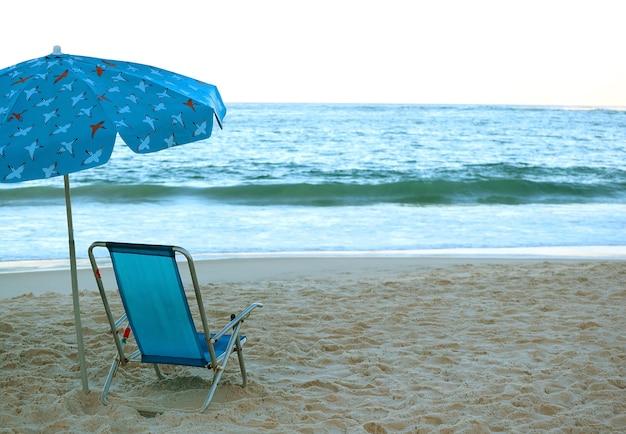 Пустой синий шезлонг и пляжный зонтик на песчаном пляже перед грохотом волн на синем океане