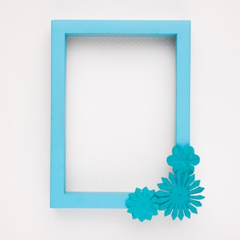 An empty blue border frame with flowers on white backdrop