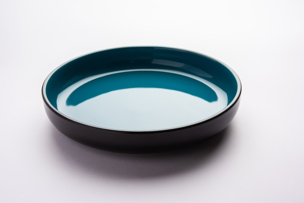 白または灰色の表面上に分離された空の青いセラミックサービングボウル