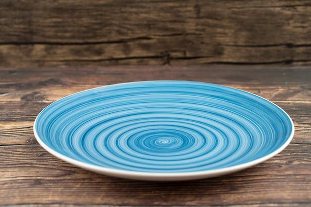 Пустая синяя тарелка на деревянном столе.