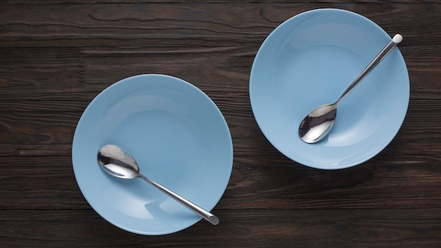 Empty blue dishes with spoons on a wooden table. top view