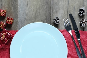 Empty Blue plate and Christmas Decoration Equipment on wooden floor.