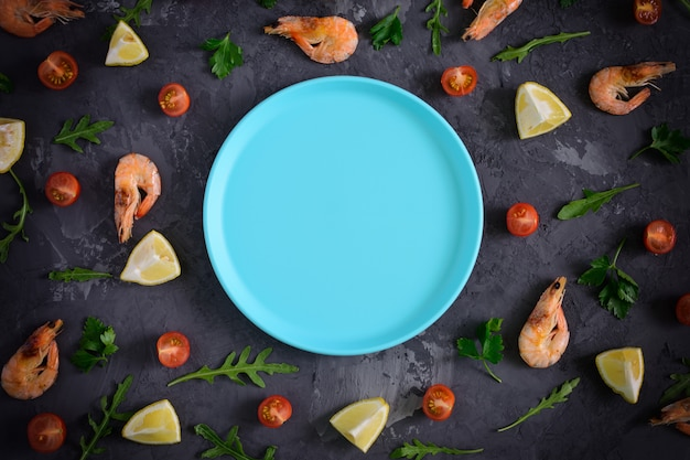 An empty blue plate lies on dark concrete texture