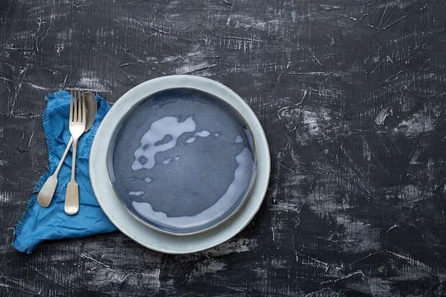 빈 파란색 접시는 포크 숟가락 테이블 냅킨과 함께 제공됩니다. 레스토랑에서 호화로운 저녁 식사를위한 빈티지 블루 플레이트. 어두운 검은 콘크리트 테이블 분필 보드 복사 공간.