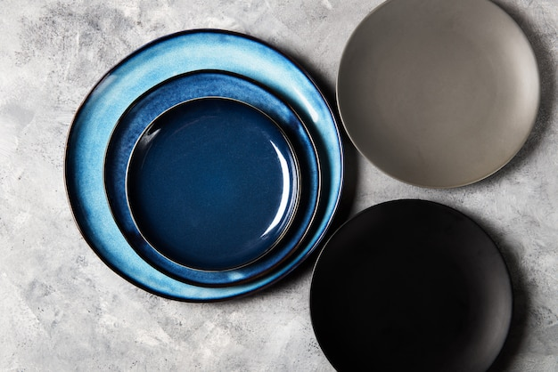 Empty blue plates on grey background