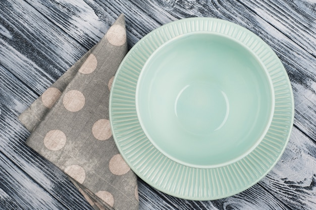 Empty blue plates and napkin over wooden table
